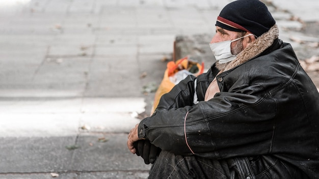 杖とコピースペースと屋外のホームレスの男性の側面図