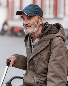 Бездомный на открытом воздухе с тростью, вид сбоку