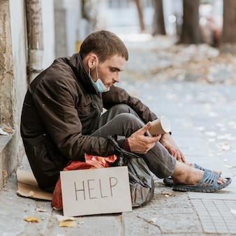 Бездомный мужчина на открытом воздухе, вид сбоку со знаком помощи и чашкой