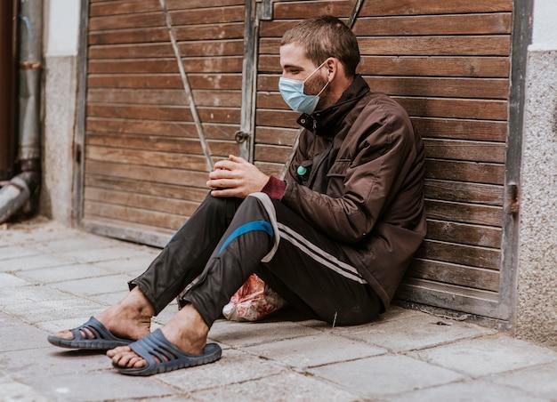 Бездомный мужчина с медицинской маской на открытом воздухе, вид сбоку