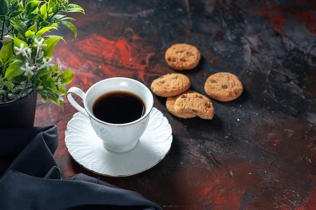 Вид сбоку на домашнее вкусное сахарное печенье и цветочный горшок с чашкой кофе на фоне темных цветов