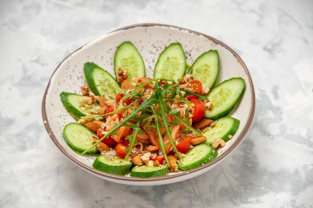 ステンドグラスの白い表面にボウルに刻んだキュウリで飾られた自家製の健康的なおいしいビーガンサラダの側面図