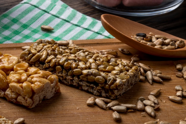 Вид сбоку мед баров с арахисом и семечками на деревянной доске на деревенском