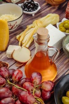 Вид сбоку меда в стеклянной бутылке с маринованными оливками свежего винограда и различных видов сыра на деревенском дереве