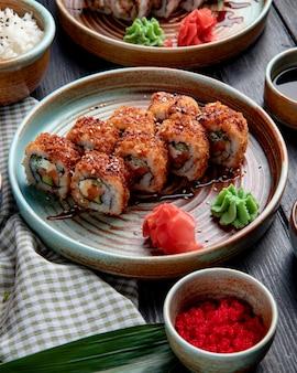 Вид сбоку горячих жареных суши роллов с лососем авокадо и сыром, подается с имбирем и васаби на тарелке на дереве