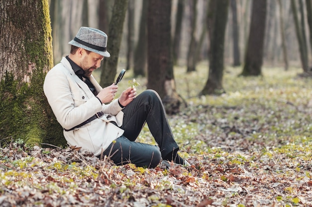 Вид сбоку умного человека, смотрящего на цветок через лупу, сидящего против дерева в лесу