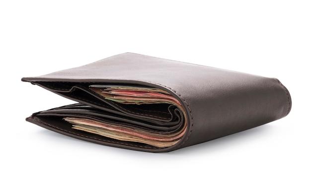 Взгляд со стороны изолированного коричневого цвета неподдельной кожи с много банкнот на белой предпосылке. концепция наличных денег и путь клиппирования фото.