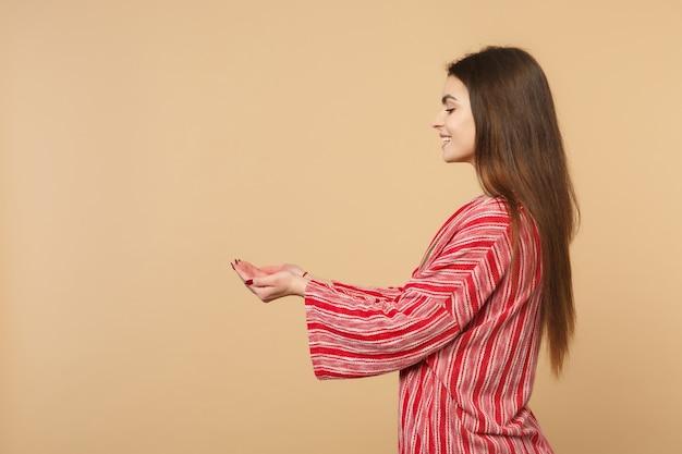 スタジオでパステルベージュの背景に分離された手で何かを保持しているカジュアルな服を着て楽しい美しい若い女性の側面図。人々の誠実な感情、ライフスタイルのコンセプト。コピースペースをモックアップします。
