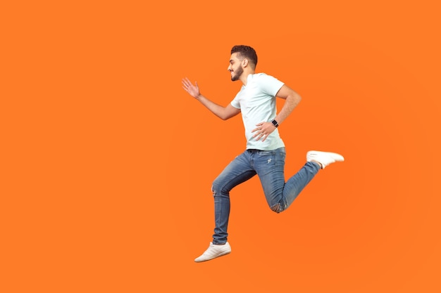 Вид сбоку радостного брюнет с бородой в кроссовках и джинсовой одежде, бегущего в воздухе, спешащего за скидками, пустого места для рекламы. закрытый студийный выстрел изолирован на оранжевом фоне