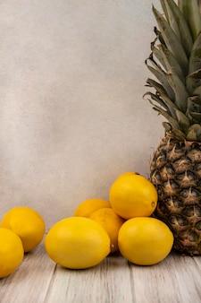 흰색 표면에 회색 나무 테이블에 고립 된 레몬과 파인애플과 같은 달콤한 과일의 측면보기