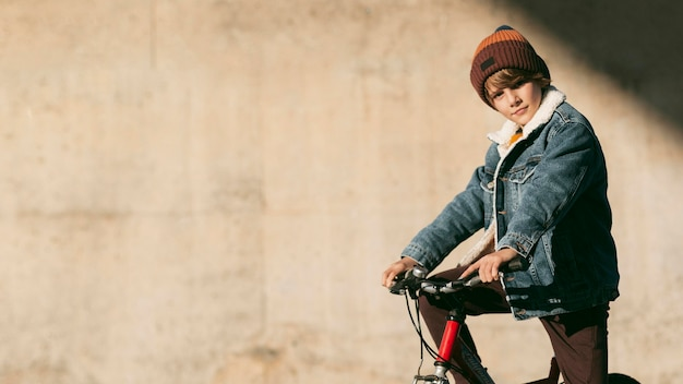 Вид сбоку ребенка на велосипеде на открытом воздухе с копией пространства