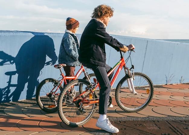 Вид сбоку на детей, вместе катающихся на велосипедах на открытом воздухе