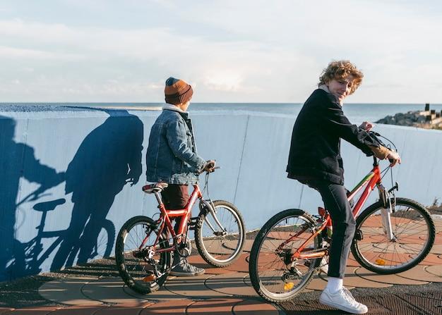 Вид сбоку детей, езда на велосипедах на открытом воздухе