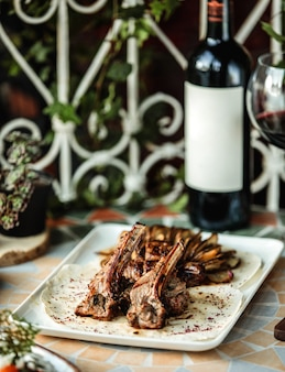 레드 와인 한 병을 테이블에 구운 감자와 양고기 갈비 케밥의 측면보기