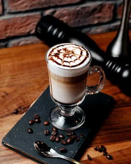 木製のテーブルにガラスのラテマキアートコーヒーの側面図