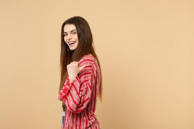 スタジオでパステルベージュの背景に分離された親指を脇に向けて、カメラを探しているカジュアルな服で若い女性を笑っている側面図。人々の誠実な感情、ライフスタイルのコンセプト。コピースペースをモックアップします。