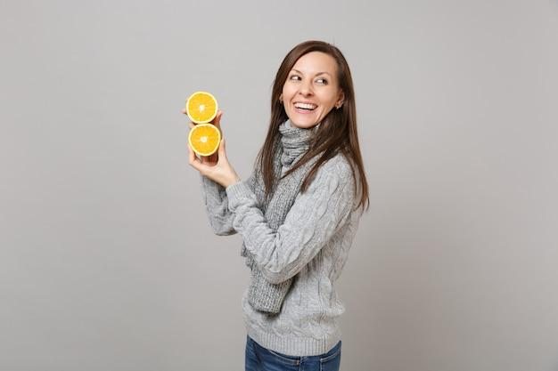 Вид сбоку смеющейся молодой женщины в сером свитере, шарфе, держащем апельсины, изолированные на сером стенном фоне. здоровый образ жизни моды, искренние эмоции людей, концепция холодного сезона. копируйте пространство для копирования.