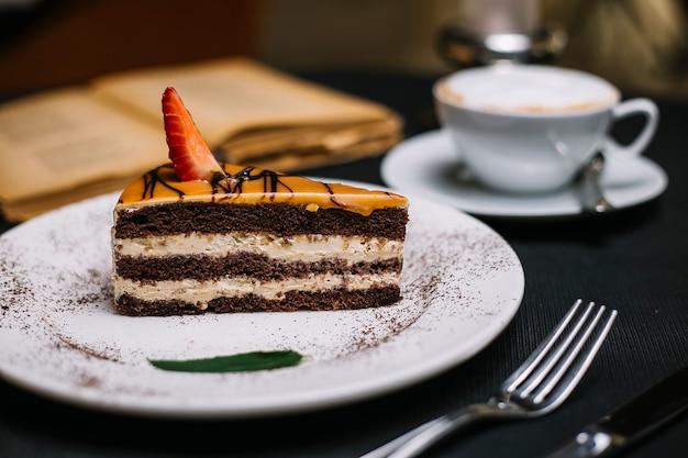 白いプレートにイチゴのスライスをキャラメルで覆われた層状チョコレートケーキの側面図