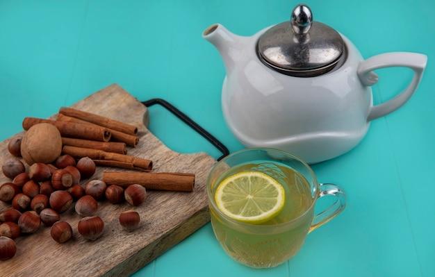 Вид сбоку лимонного сока с долькой лимона в стеклянной чашке и орехами с корицей и грецким орехом на разделочной доске с чайником на синем фоне
