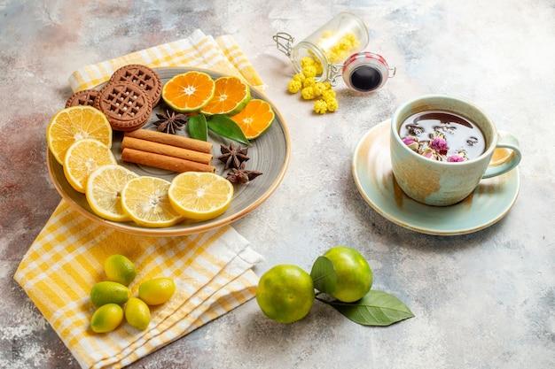 Вид сбоку ломтиков лимона, корицы, лайма на деревянной разделочной доске и печенья на белом столе