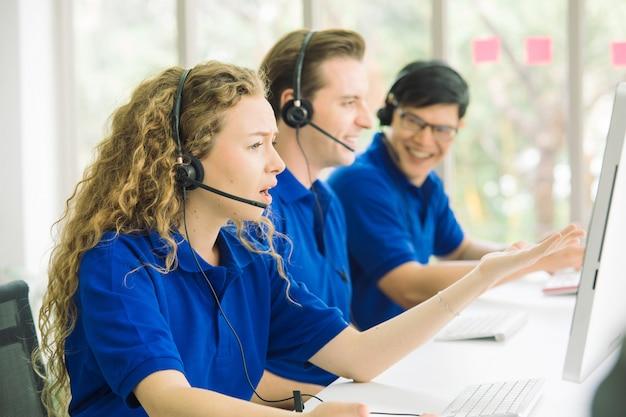 コールセンターのラインの側面図は、笑顔で近代的なオフィスのコンピューターで作業しています。