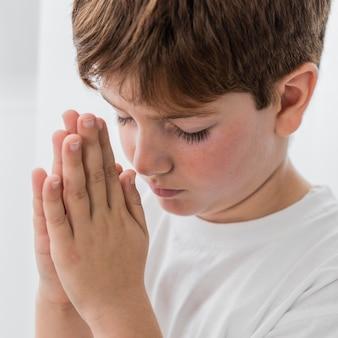 Маленький мальчик молится, вид сбоку