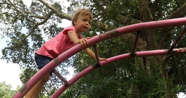 녹색 공원에서 놀이터에 금속 사다리에 등반 작은 호기심 소년의 측면보기