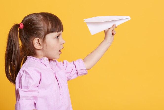 손에 흰 종이 비행기와 함께 포즈를 취하는 작은 귀여운 여자 아이의 모습