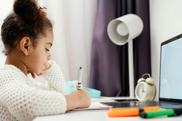 Маленькая девочка, посещающая онлайн-школу дома, с помощью ноутбука, вид сбоку
