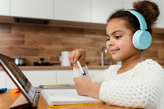 タブレットとヘッドフォンでオンライン学校中の少女の側面図