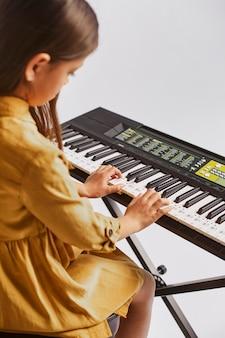 Маленькая девочка учится играть на электронной клавиатуре, вид сбоку