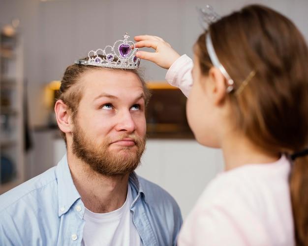 Маленькая девочка надевает диадему на голову отца, вид сбоку