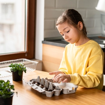 Маленькая девочка сажает семена дома, вид сбоку