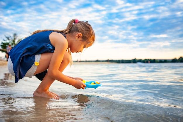 해변 모래에 서있는 작은 파란색 수영장에서 작은 고무 노란색 오리를 가지고 노는 작은 사랑스러운 소녀의 측면보기
