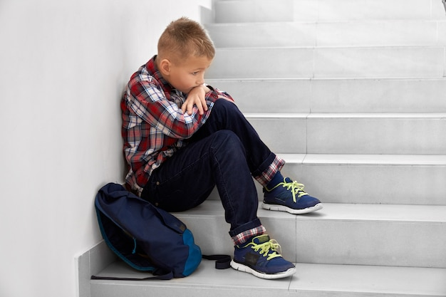Вид сбоку маленького школьника, сидящего в одиночестве на лестнице в школе и опирающегося на колени