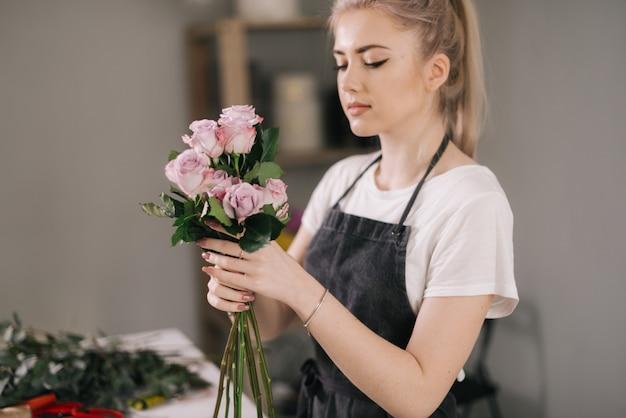 앞치마를 입고 사랑스러운 젊은 여성 꽃집의 측면보기 꽃다발 fromfresh 장미를 조립