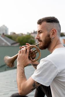 屋上でコルネットを演奏する男性アーティストの側面図