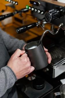 Бариста-мужчина готовит молочную пену для кофе, вид сбоку