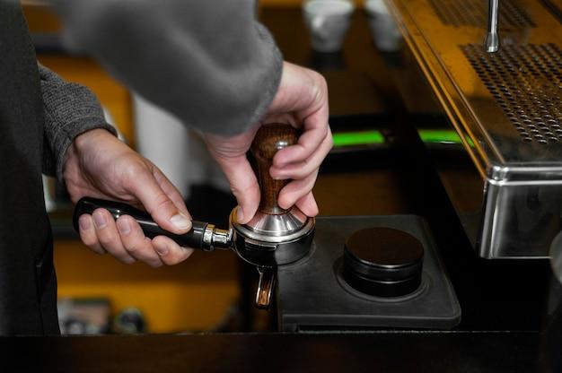 コーヒーマシンと男性バリスタの側面図
