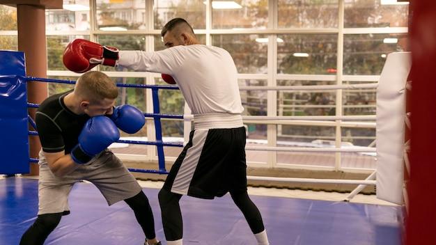 トレーナーと練習している男性ボクサーの側面図