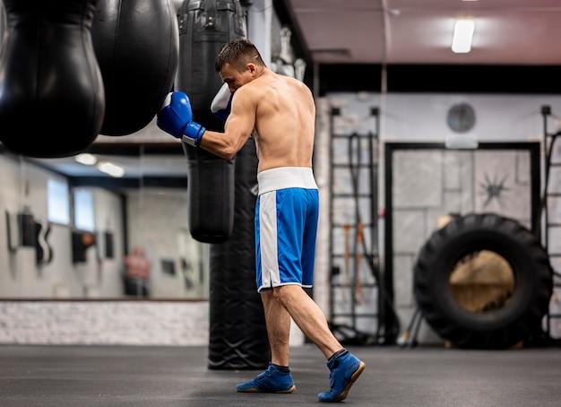 保護手袋と男性のボクサーのトレーニングの側面図