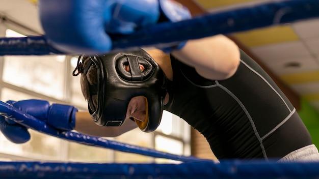 リングに手袋とヘルメットを持つ男性ボクサーの側面図