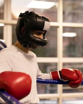 リングにヘルメットを持つ男性ボクサーの側面図