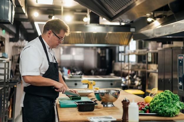 Вид сбоку мужской шеф-повар на кухне готовит овощи