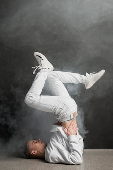 Вид сбоку танцор в позе танца с дымом