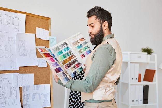 Вид сбоку мужской моды, работающей с цветовой палитрой в ателье