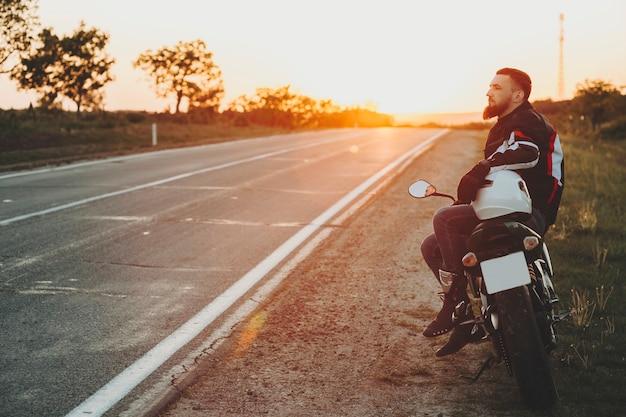 空の高速道路のバックライト付きの背景に日没時に道端でヘルメットに手を置くオートバイに横に座っている保護具の男性の側面図