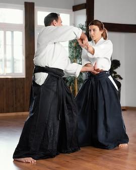 練習場で女性の訓練生と一緒に訓練する男性の武道のインストラクターの側面図