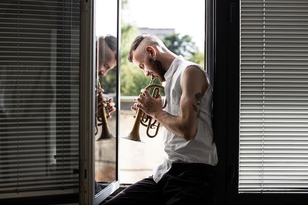 ウィンドウでコルネットを演奏する男性ミュージシャンの側面図