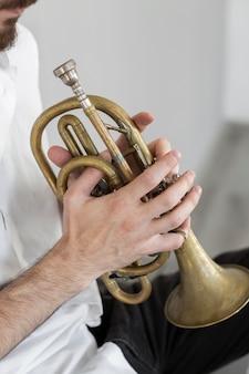 コルネットを演奏する男性ミュージシャンの側面図